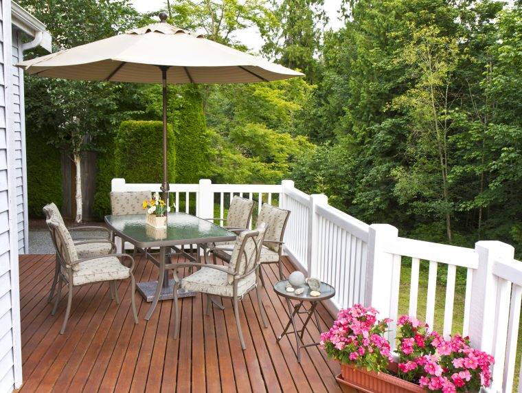 Outdoor patio setup on cedar wood deck with trees in background
