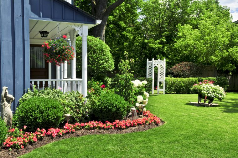 Nice home landscaping with a row of red flowers