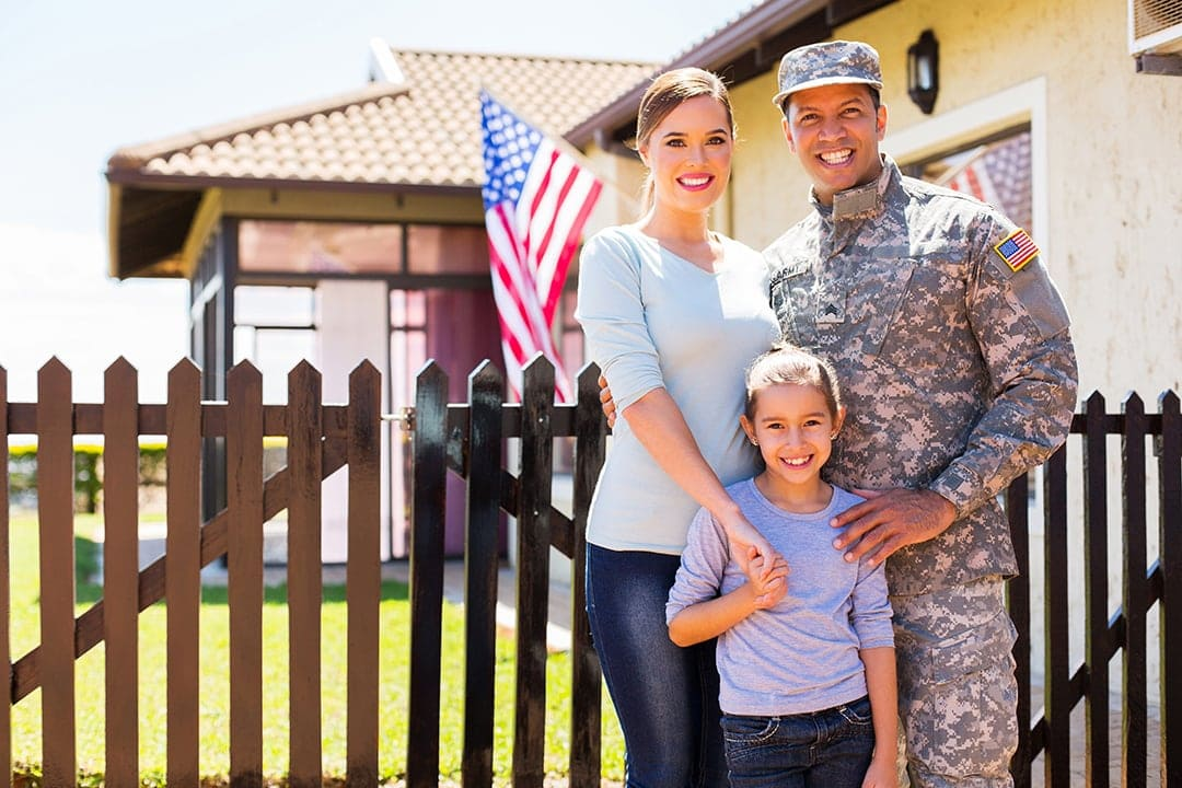 A smiling veteran and his family in front of their new home