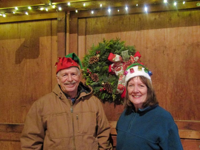 Ken and Libby Guthrie wearing holiday hats with their finished Christmas wreath